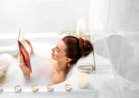 woman enjoying self care in a bath with candles reading a book